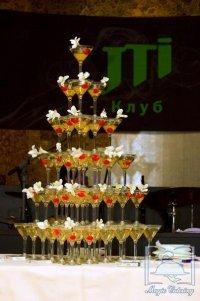 на столах высились фруктовые пирамиды и пирамиды с шампанским.